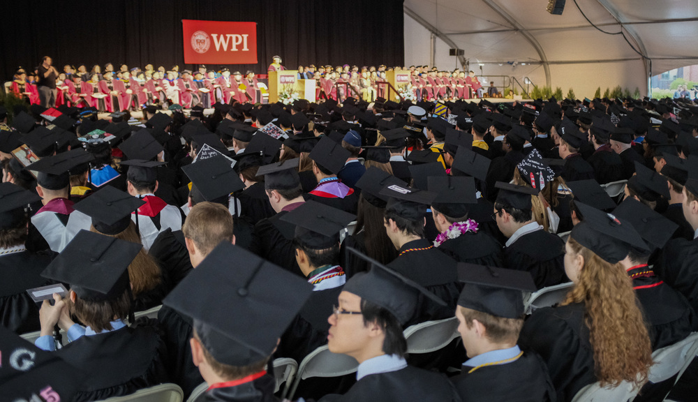 A wide shot of the 2018 Commencement ceremony. Rows of graduates are in the shot, facing toward the stage where a large WPI banner is hanging and speakers are addressing the crowd.