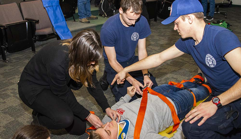 Students from the EMS squad practice techniques on safely securing someone to a stretcher.