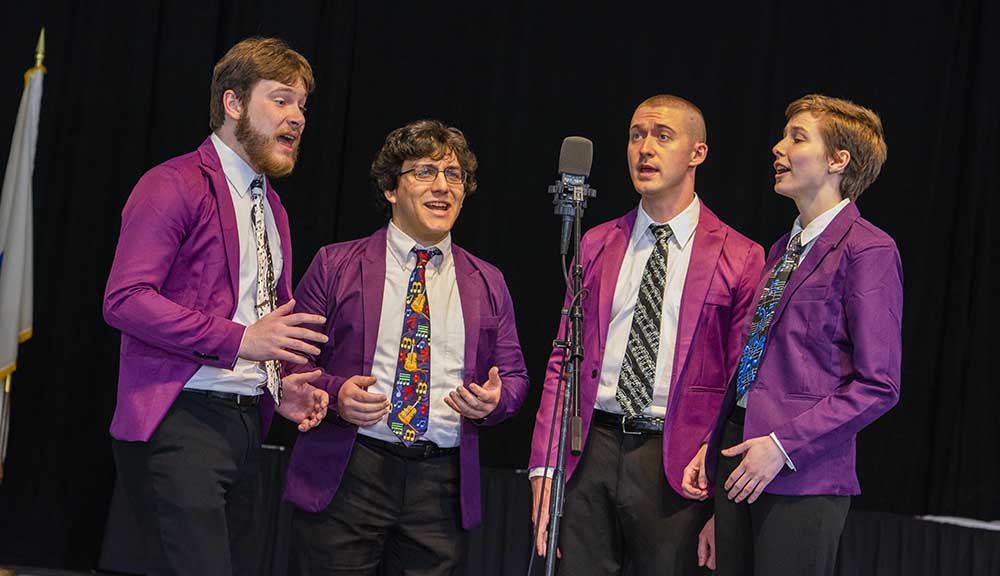 Four students in matching purple suit jackets gather around a microphone to sing during the baccalaureate ceremony.