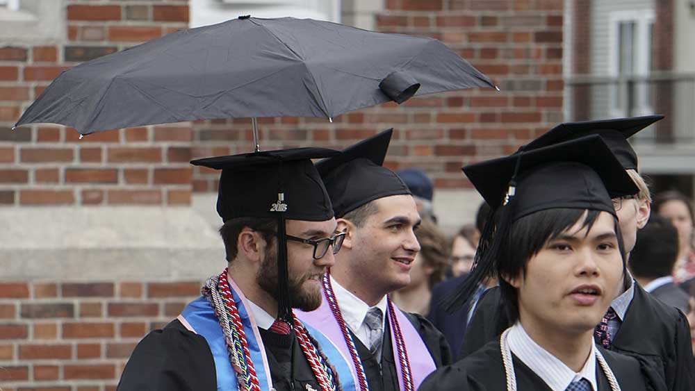 A student models his mortarboard, which has an umbrella affixed to the top, during a rainy undergraduate Commencement.