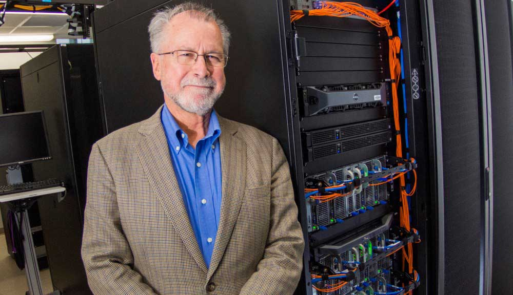 Homer Walker stands in front of a high-performance computing system. He's wearing glasses, a blue button-down shirt, and tan suit jacket, and is smiling.