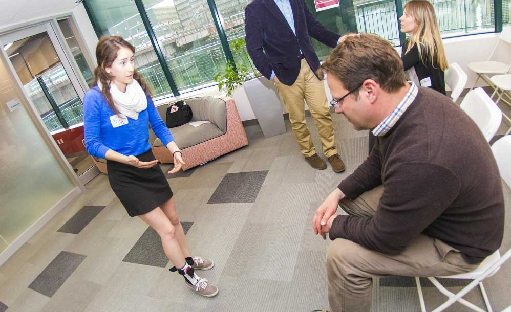 Julia Dunn demonstrates her team's device designed to improve the gait of someone with foot drop as visitors observe.