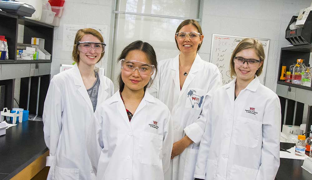 Natalie Farny and three students stand in their lab, wearing safety equipment including glasses and white lab coats; they're all smiling.