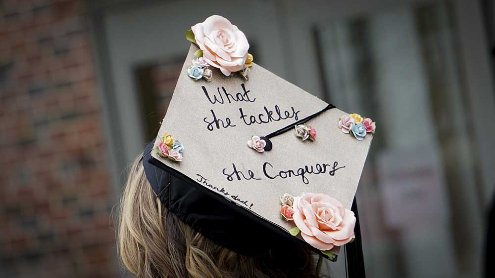 "A closeup of a graduation cap decorated with flowers and script reading, ""What she tackles, she conquers. Thanks, Dad!"""