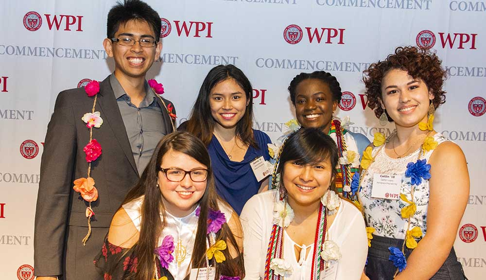 Students gather and smile in front of a WPI background during the OMA Graduation Celebration.