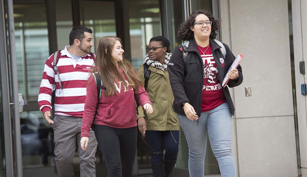 Four students exit a building on WPI's campus. Most are wearing WPI gear, and they're conversing with each other.