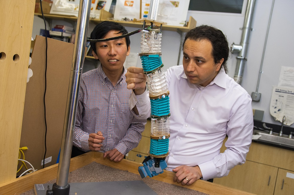 WPI professor Cagdas Onal (right) and PhD candidate Junius Santoso examine a soft manipulator robot in the Soft Robotics lab at WPI.