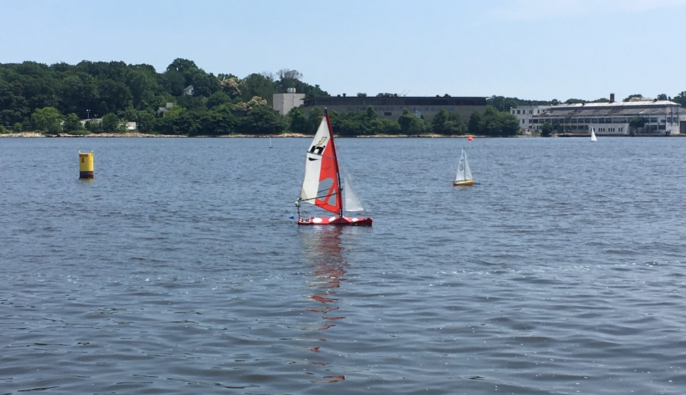 WPI's sailboat (center) crosses the finish line on another autonomously completed lap during the six-hour endurance test in 2017.