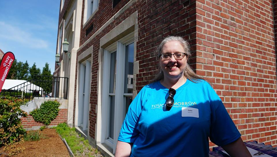 Patty A. MacInnes smiles in front of the Higgins Lab while wearing a nametag and blue TouchTomorrow volunteer T-shirt.