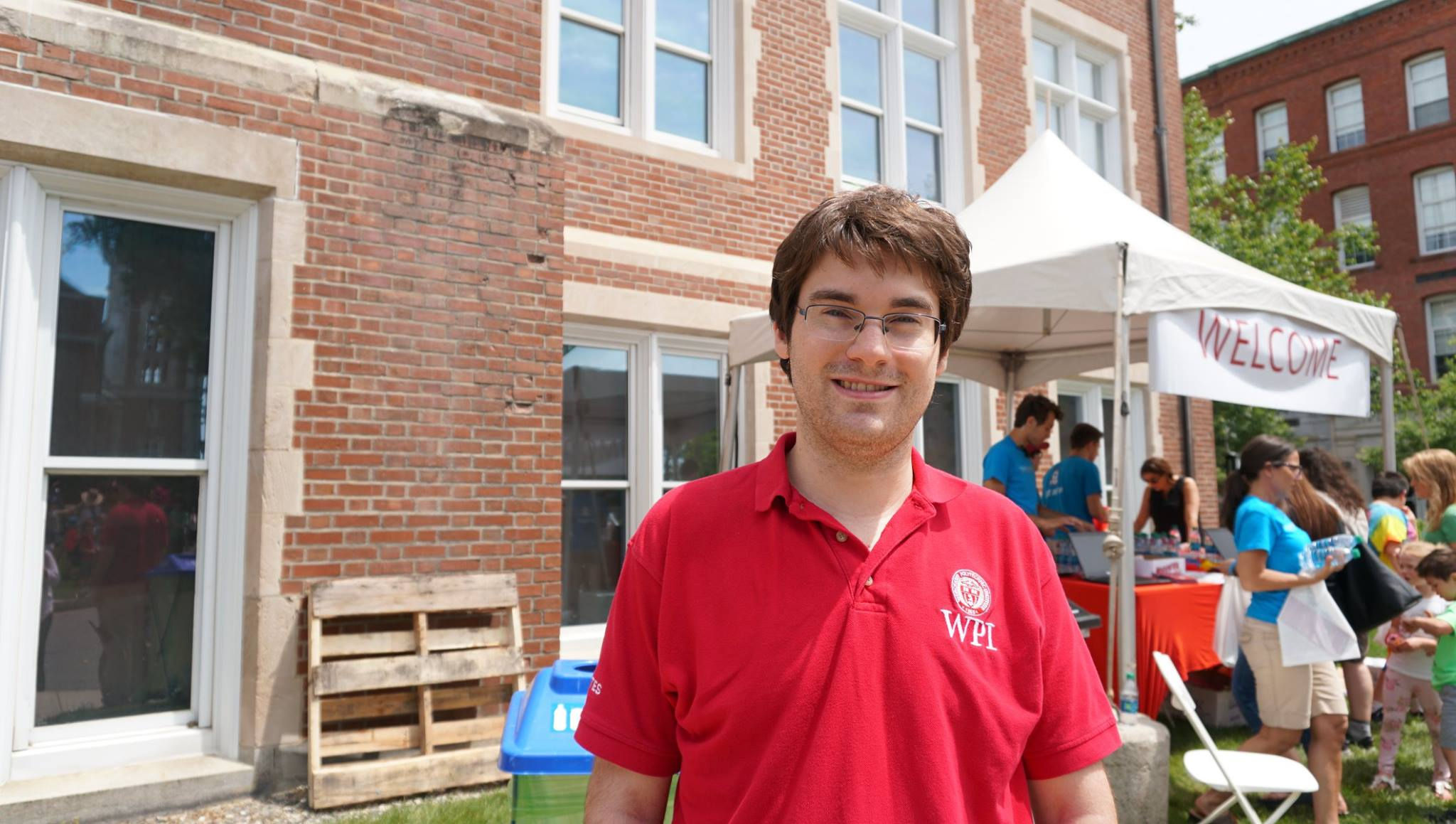 Nick Sloat stands in front of Higgins Lab. He's smiling and is wearing glasses and a red WPI polo shirt.