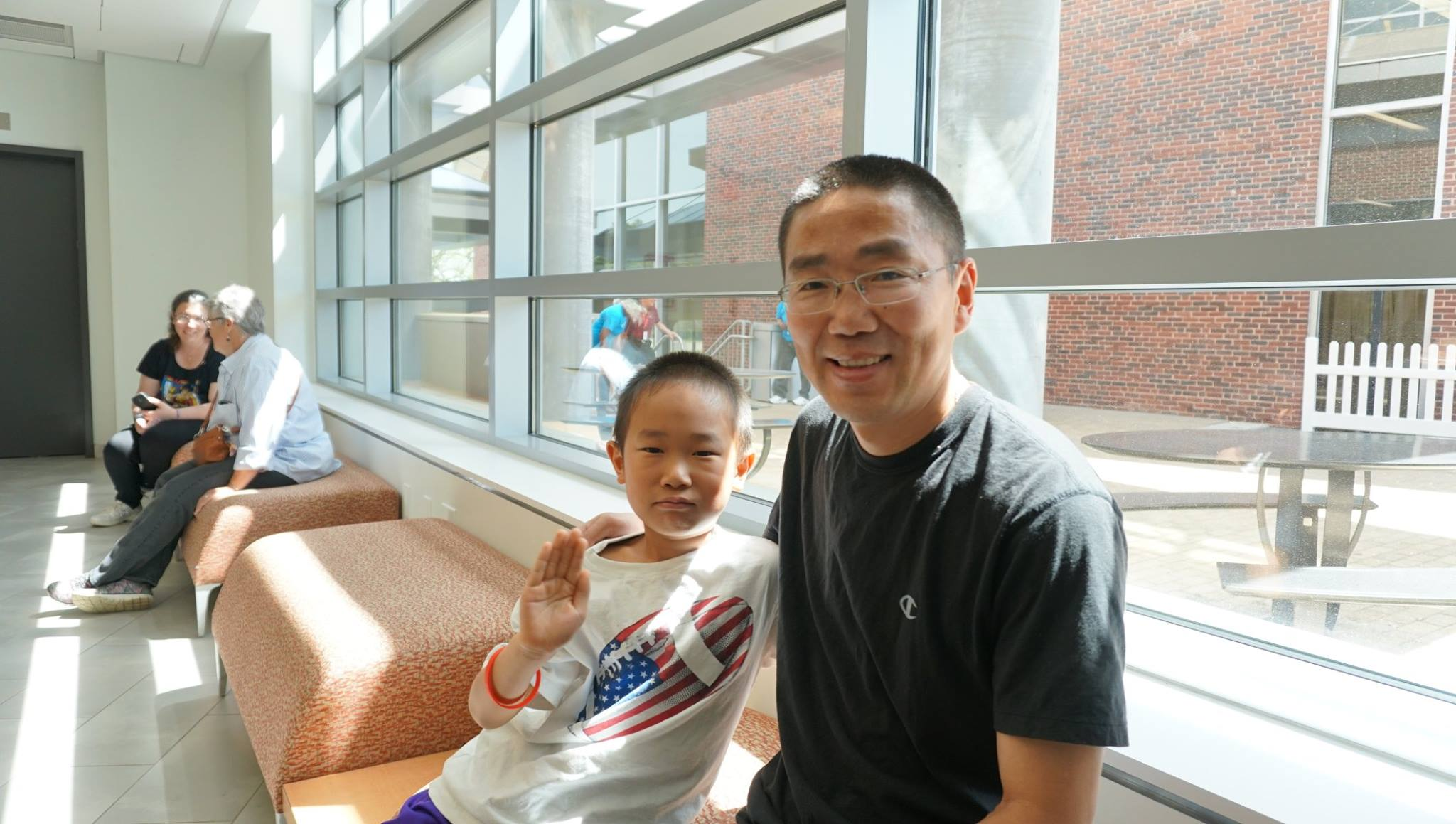 A son and father relax in the lobby of the Sports & Rec Center with several glass windows behind them.