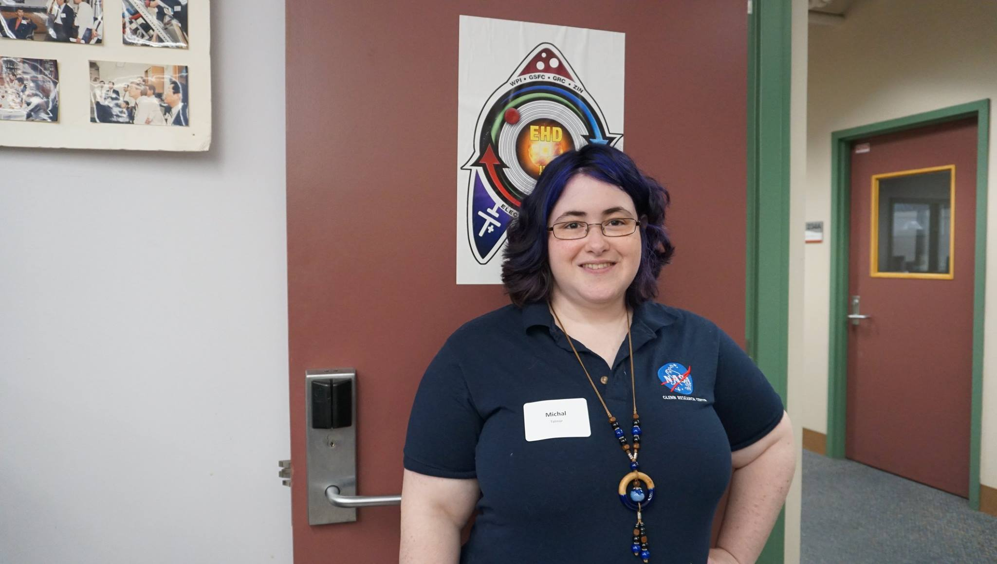 Michal Talmor smiles in a doorway. She's wearing a dark blue polo, lanyard, and glasses, is smiling, and has dark brown and purple hair.