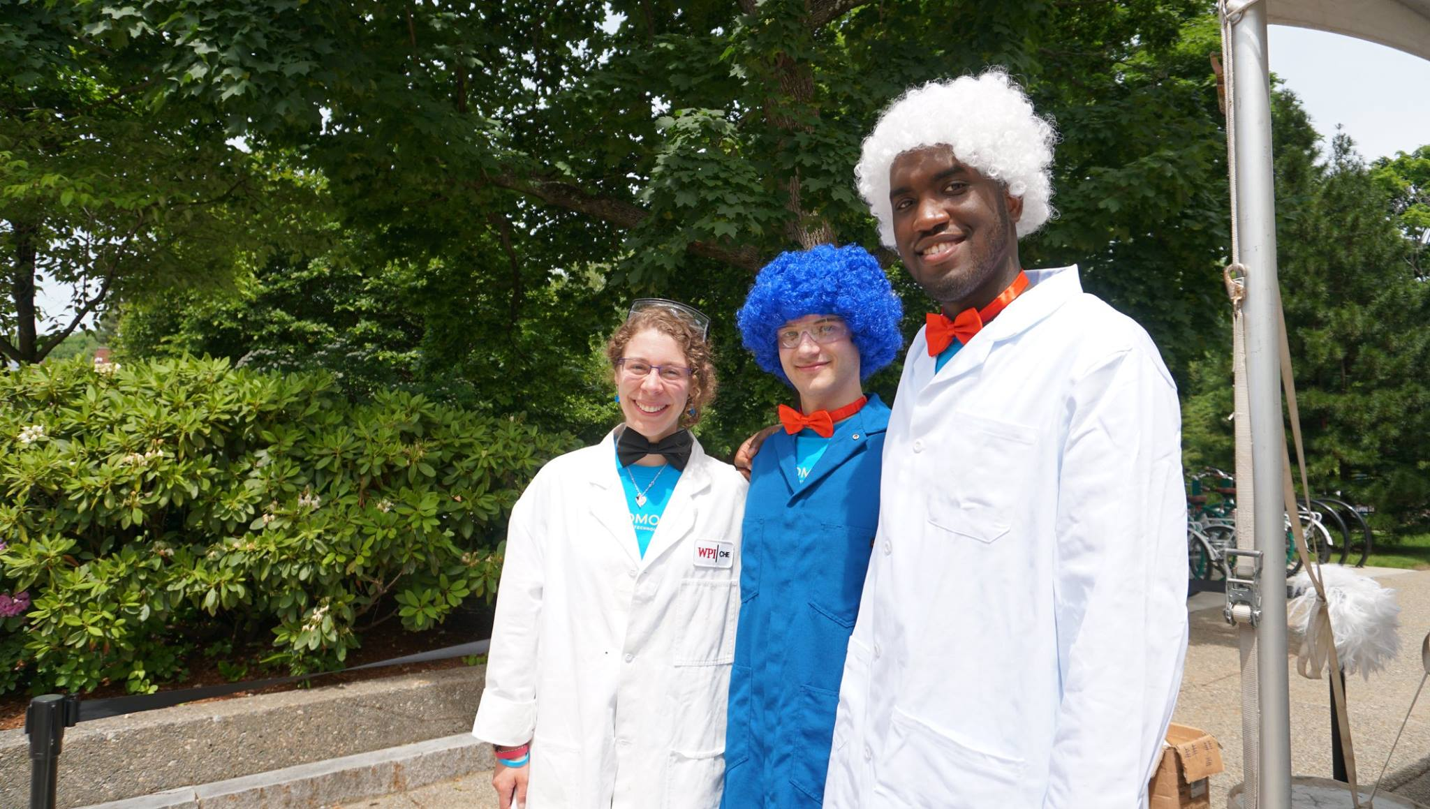 "Three students stand outside together in their lab coats. All three are wearing bowties, and two have wigs on and are dressed as ""wacky scientists."""