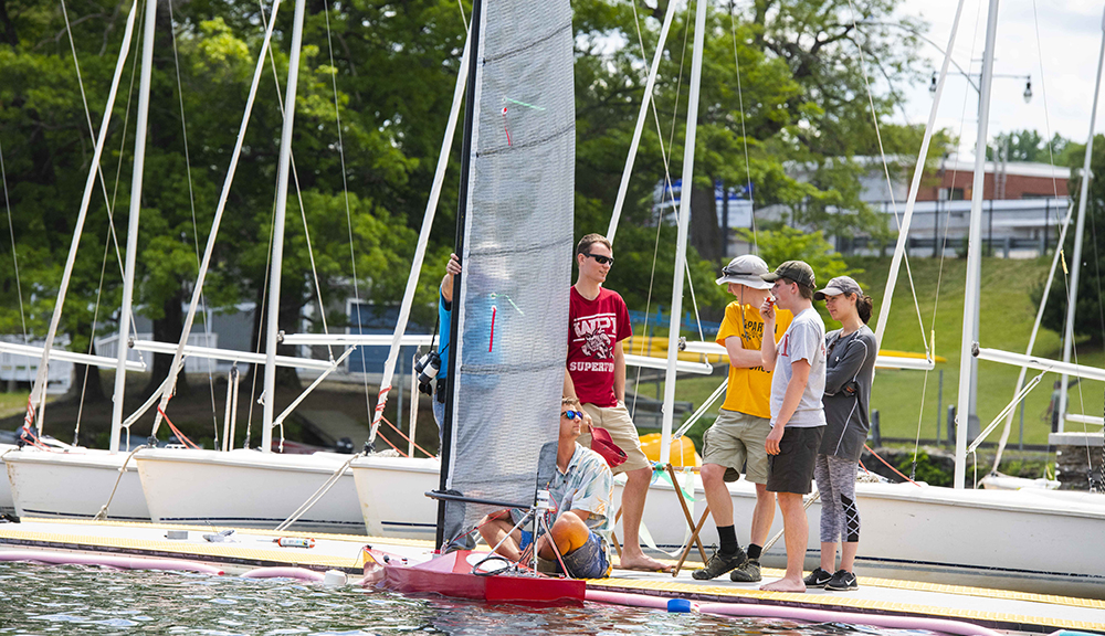Members of the WPI SailBot team gather on the dock in front of their bot as they wait for the competition to begin.