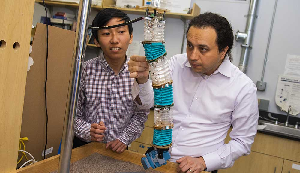 PhD candidate Junius Santoso (left) and professor Cagdas Onal test out an origami-inspired robot.