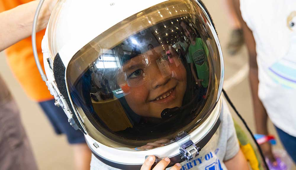 A child smiles while wearing an astronaut helmet during TouchTomorrow.
