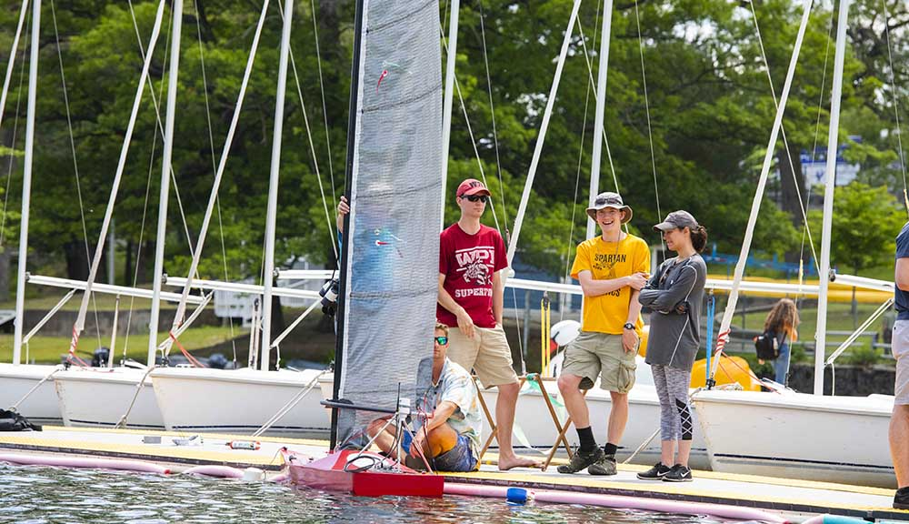 Several WPI students gather at the dock for the annual SailBot competition, with their sailbot in the water in front of them.