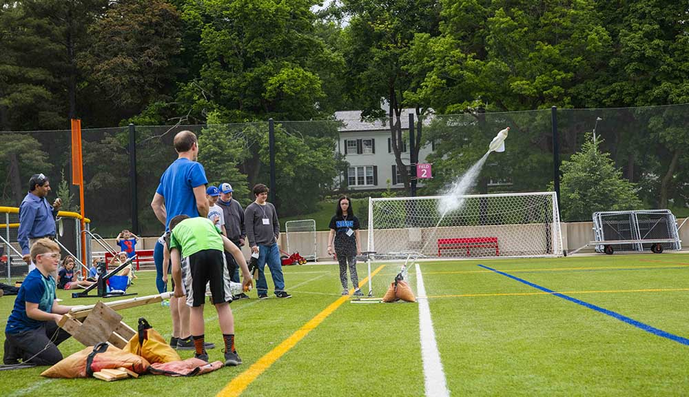 Students gather on top of the rooftop field for the water rocket launch event.