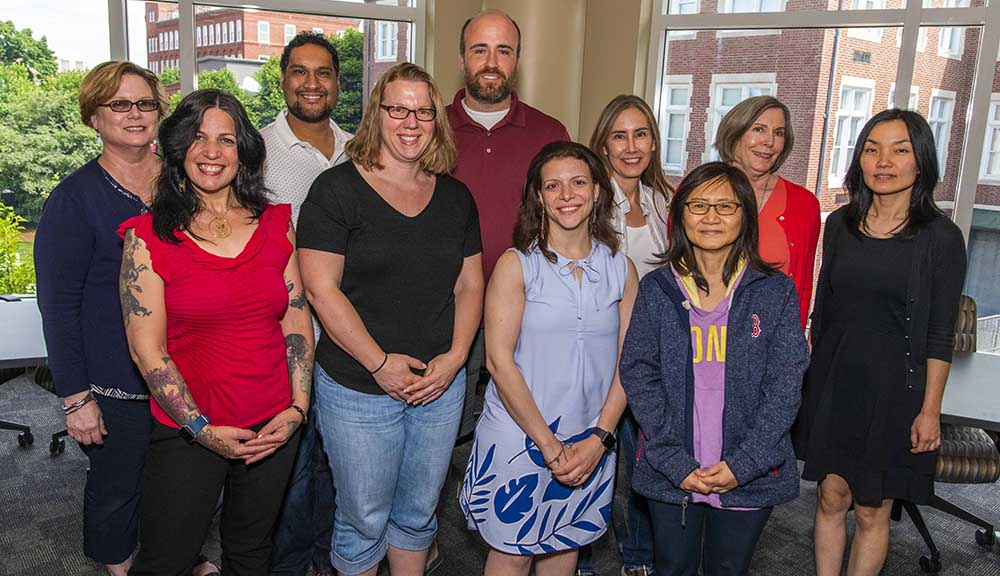 A group photo of the IPBL team that attended this year's Institute on Project-Based Learning. They're all wearing casual clothing, and are standing in front of large windows in the Rubin Campus Center.