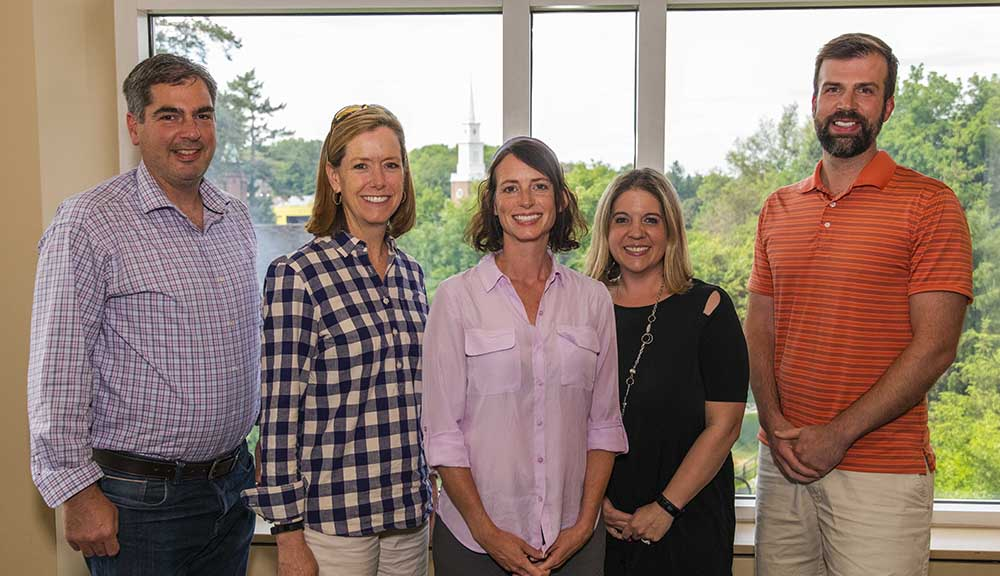The team from Wake Forest stands in front of large windows in the Rubin Campus Center during the 2018 Institute on Project-Based Learning. They're smiling and wearing business casual attire.