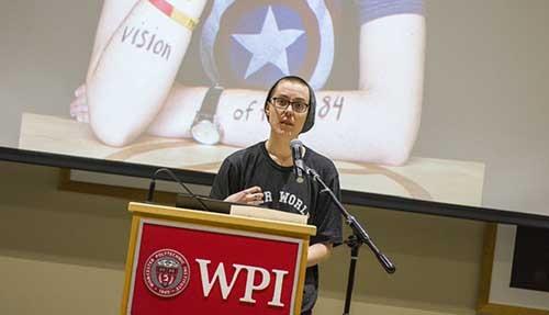 Speaker talking about art-on-skin program at WPI podium