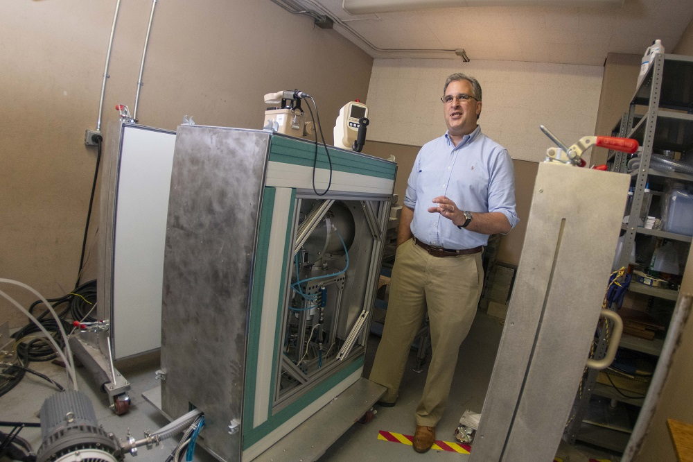 WPI professor David Medich stands next to the neutron generator he is developing for medical imaging.