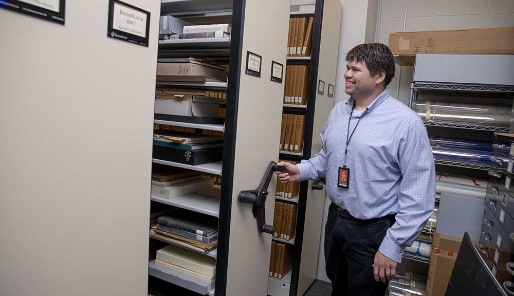 A library staff member demonstrates the new compact shelving that was installed over the summer.
