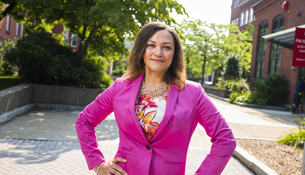 Bonnie Walker stands in the center of campus with her hands on her hips, the sunlight streaming in from behind her. She's wearing a pink blazer and white, pink, and orange patterned blouse.
