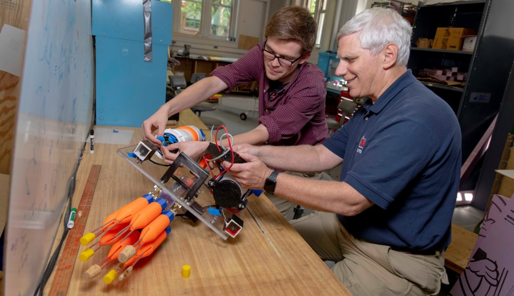 William Godsey '18, left, and Bradley Miller, associate director of WPI's Robotics Resource Center, examine the lionfish harvesting robot built by Godsey and his project team.