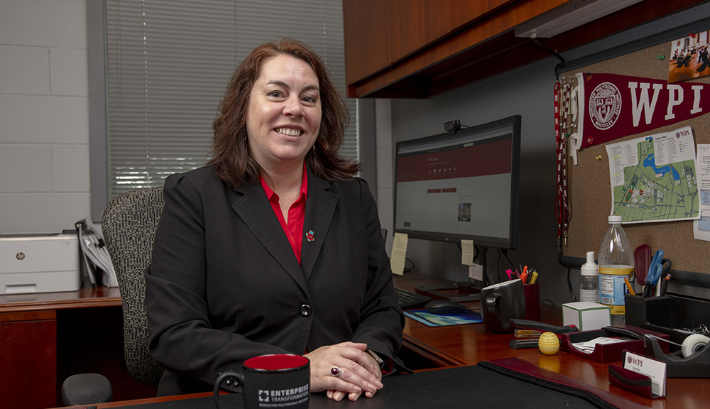 Patty Patria sits at her desk in the IT office. She's smiling and is wearing a black blazer and red shirt with her computer and a WPI pennant in the background.