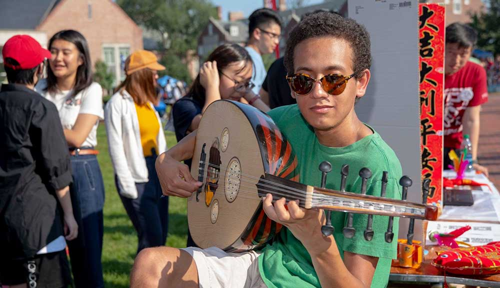 A student wearing sunglasses and a green shirt plays a musical instrument on the Quad during the Activities Fair.