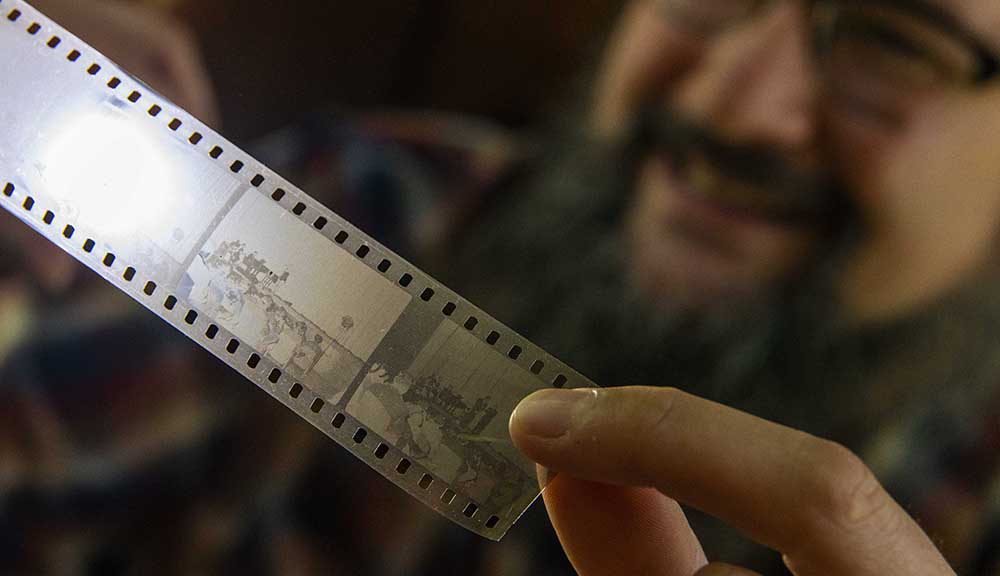 Aaron Sakulich holds a film strip up to the light while smiling in the background.
