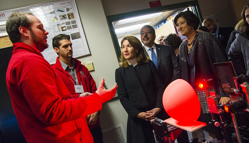 WPI researchers explain their latest technology to Karyn Polito and other guests while Laurie Leshin looks on.