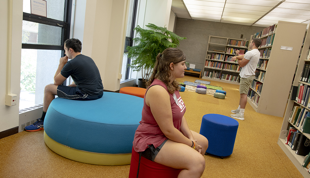 Three students engage in the library's new reflection space by stretching and meditating.