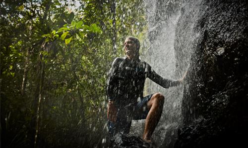 Petrini stands beneath waterfall