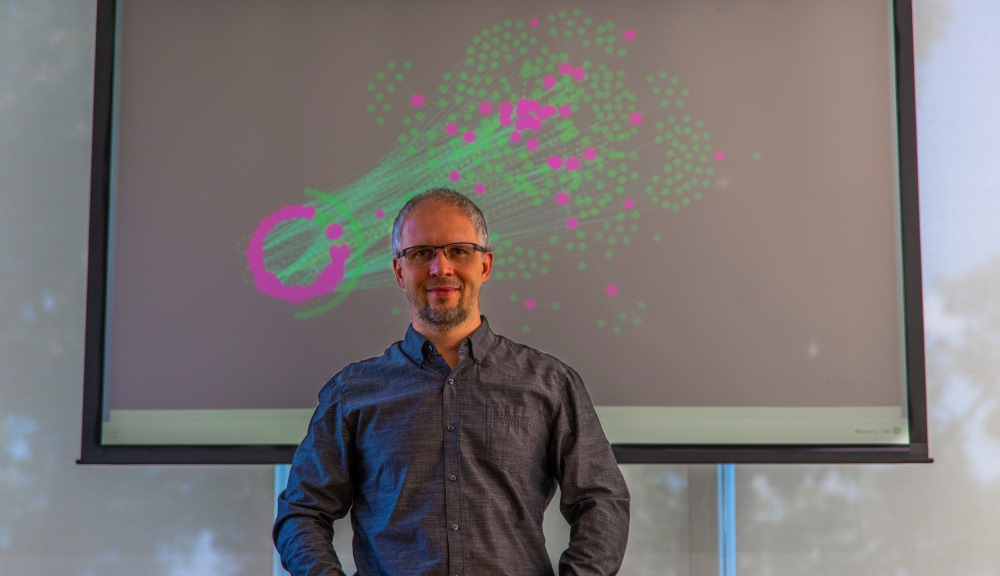 Dmitry Korkin stands before a depiction of a network of proteins that are affected by type 2 diabetes (in pink). The lines represent protein-protein interactions that are expected to affected by the mutations that are linked to types 2 diabetes.