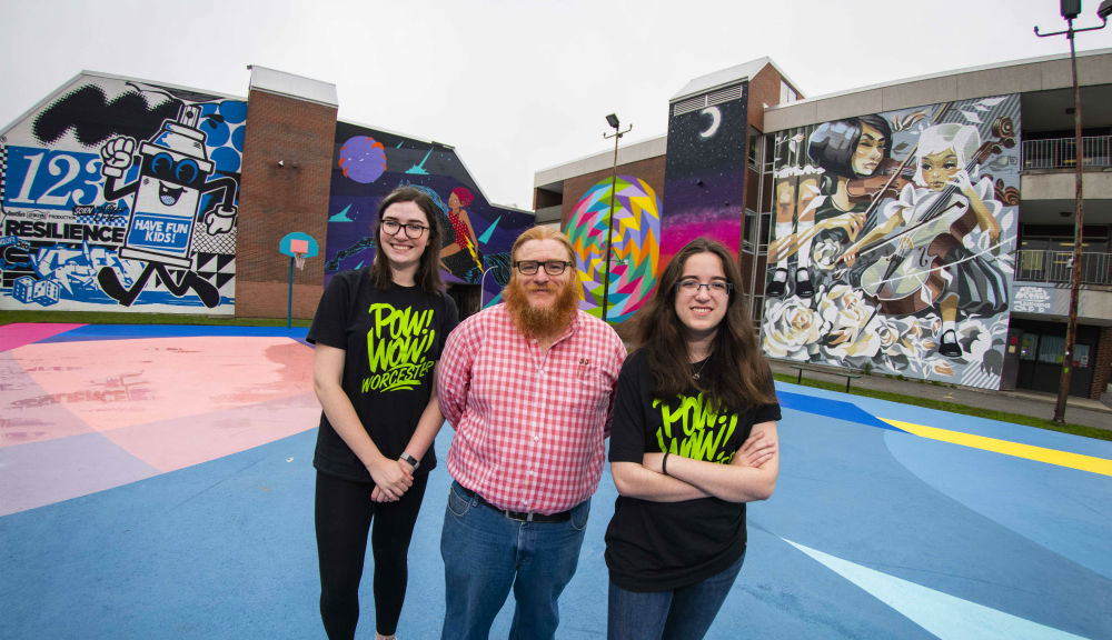 Sarah Kwatinetz, Joseph Cullon, and Brittany Goldstein stand in front of two of the many murals now decorating Worcester as part of Pow! Wow! Worcester.
