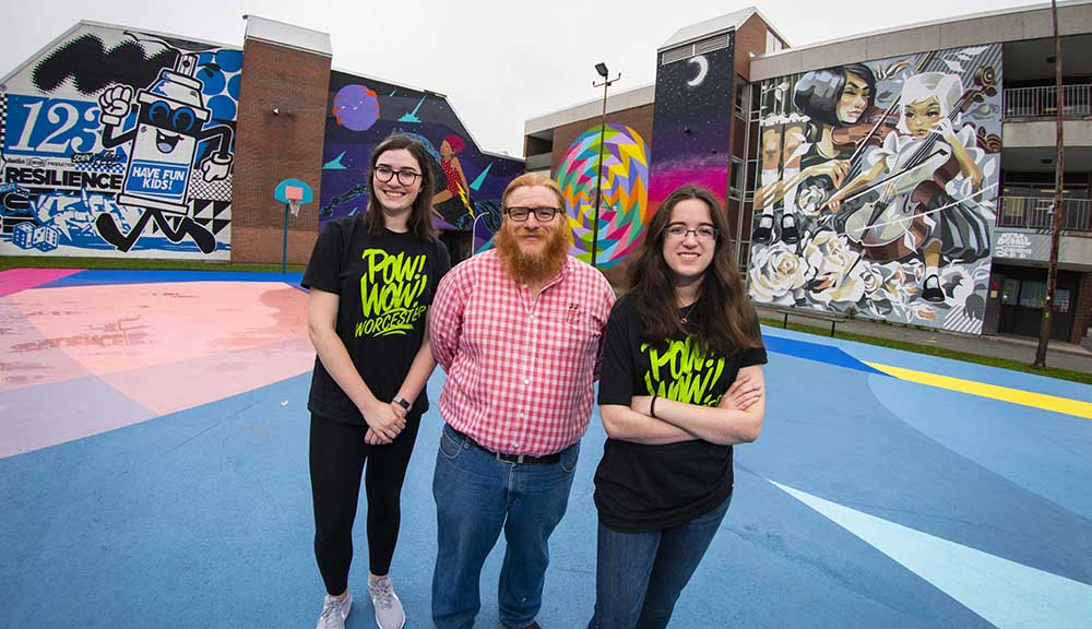 Sarah Kwatinetz '21 (left), professor Joseph Cullon, and Brittany Goldstein '21 in front of several murals from POW! WOW! Worcester.