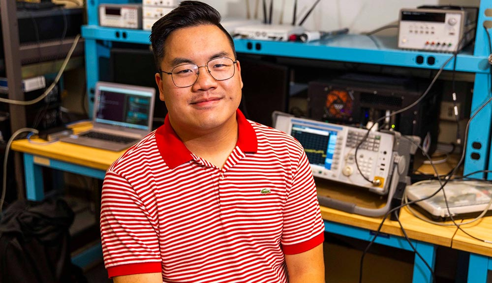 Max Li sits in a lab with a variety of tech equipment behind him. He's wearing glasses and a red and white striped shirt, and is smiling.