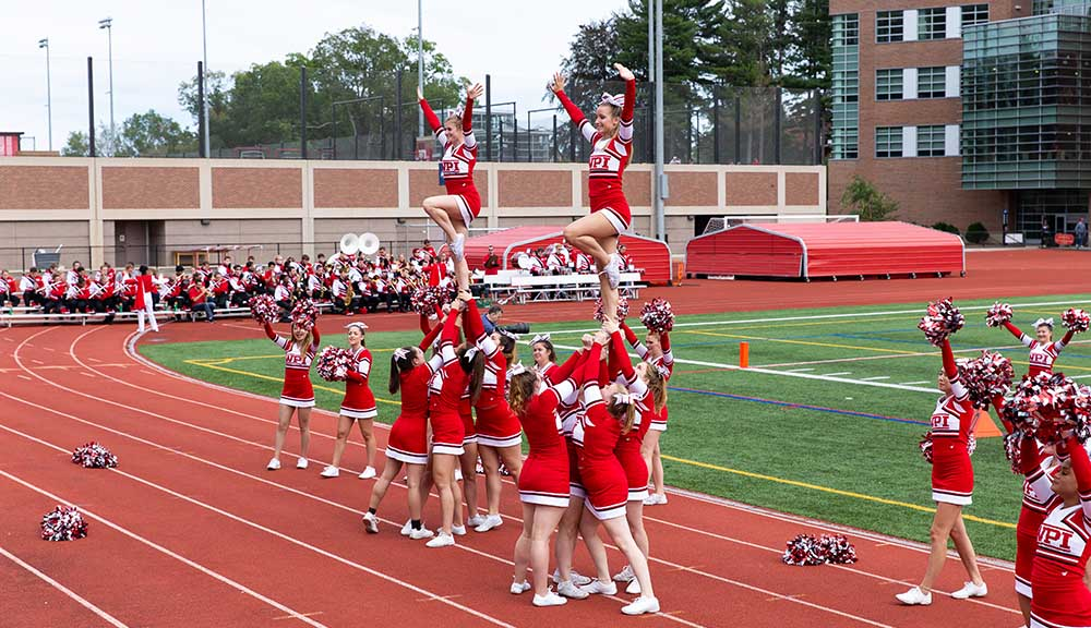 WPI cheerleaders jazz up the crowd during a football game.