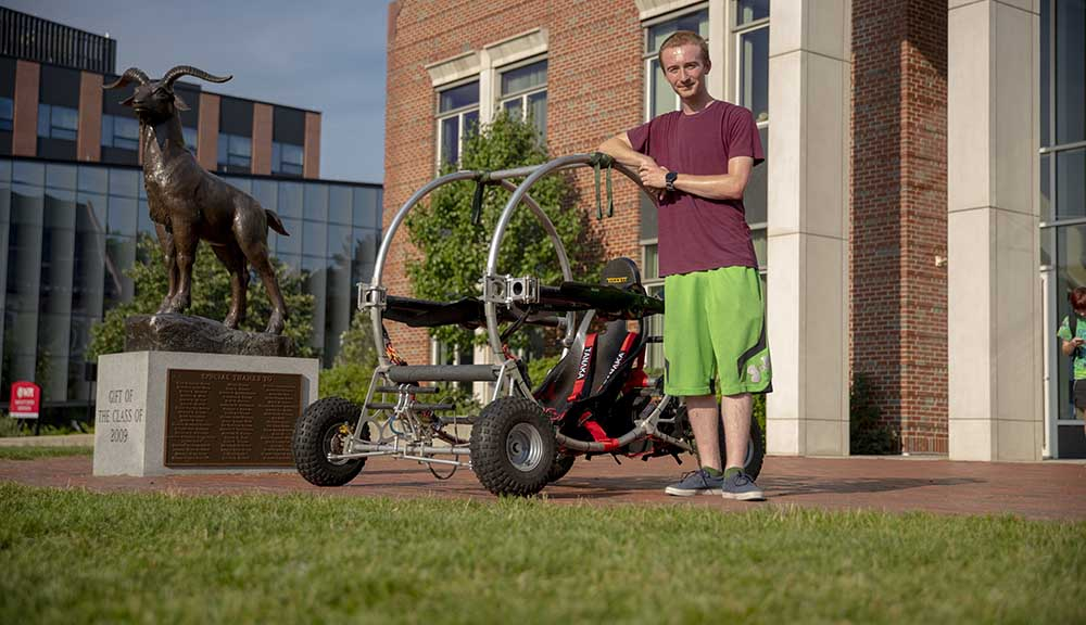 Jeremy Trilling poses with his self-constructed electric flying vehicle outside of the Bartlett Center.