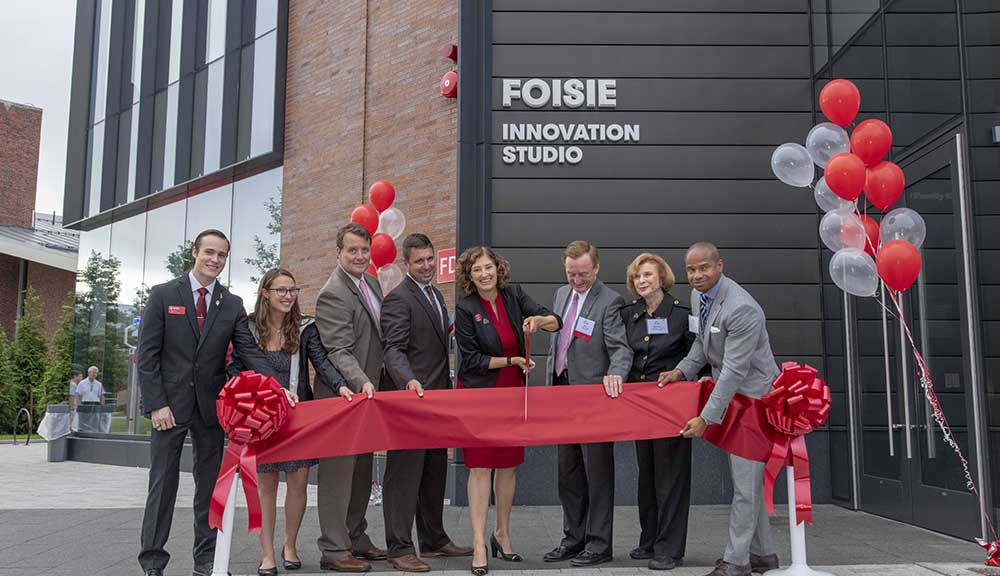 Laurie Leshin prepares to cut a red ribbon signifying the grand opening of the Foisie Innovation Studio while donors, alumni, and other officials look on.