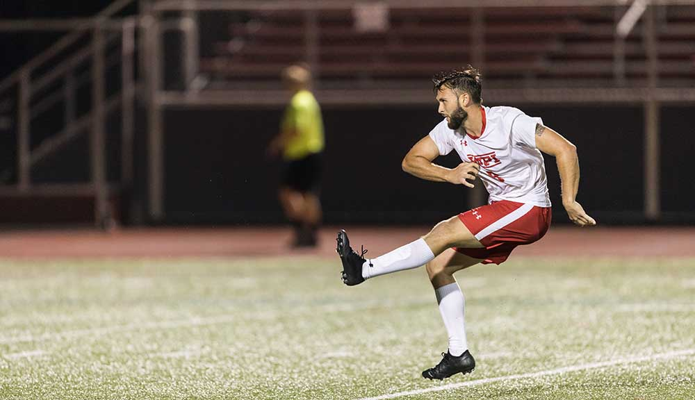 A WPI soccer player shoots a winning goal.