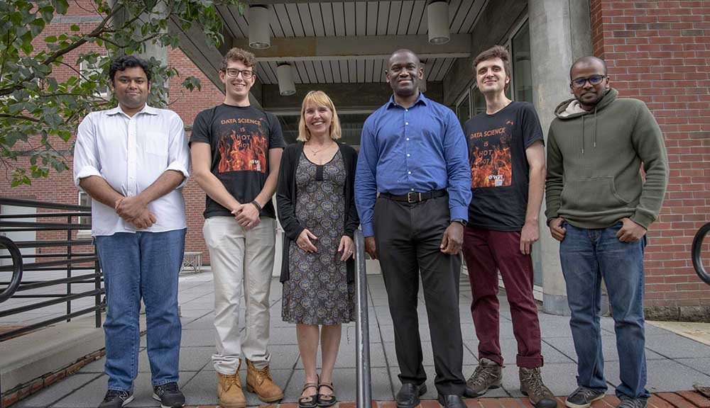 A team of WPI researchers stands together outside one of WPI's academic buildings.