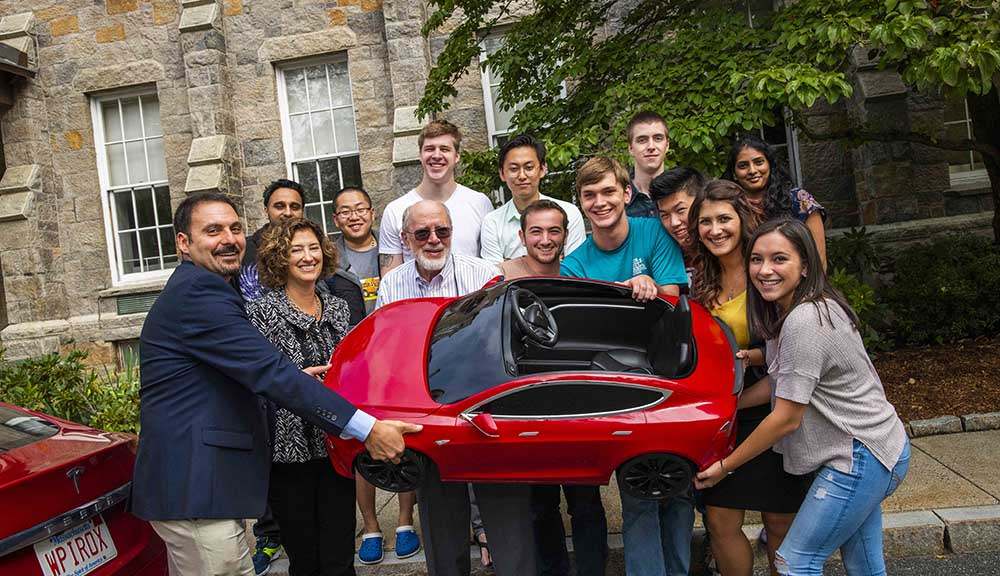 An MQP team poses with a mini Tesla that they hope to turn into a self-driving car by Commencement.