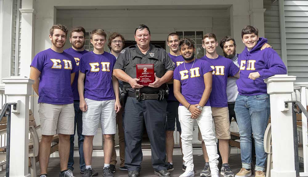 Officer Robert Vandal holds his award with brothers from Sigma Pi outside of their fraternity house.