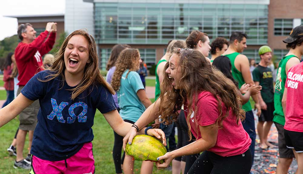 Two students, one holding half of a watermelon, laugh while participating in the annual Watermelon Bash during Family Weekend.