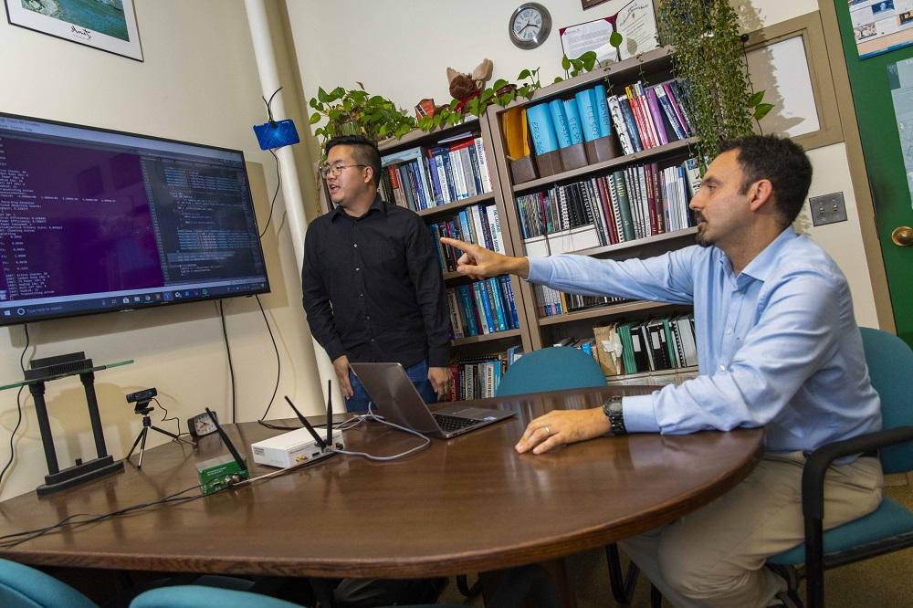 WPI professor Alex Wyglinski (right) and graduate student Max Li are using techniques to improve wireless communications in space.