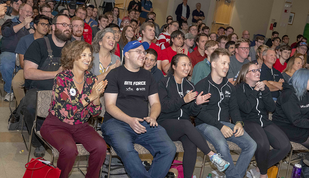 Members of team Bite Force sit and cheer with Laurie Leshin and other members of the WPI community during the BattleBots viewing party in the Odeum last Friday.