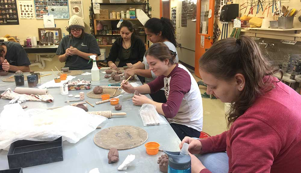 Students gather around a table to sculpt projects out of clay during last year's WinterSession.